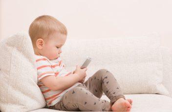 Barn sitter med smarttelefon